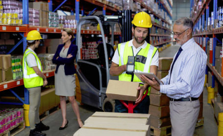 Warehouse manager holding digital tablet while male worker scanning barcode